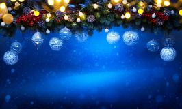 Art Christmas holiday decoration; Fir tree Branches and holiday light. On blue snowy background stock photo
