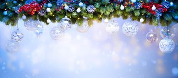 Art Christmas holiday decoration; Fir tree Branches. And holiday light on blue snowy background stock photography