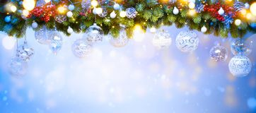 Art Christmas holiday decoration. Fir tree Branches and holiday light on blue snowy background royalty free stock image