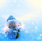 Art Christmas snowman and sparklers on blue snow background stock photography