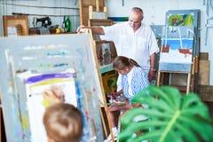 Art Class for Children. Portrait of senior  art teacher watching children painting during art class in school Royalty Free Stock Photos