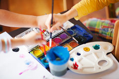 In art class. Close up image on children using different colours in art class, shallow depth of field royalty free stock photos