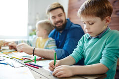Art class with male teacher. Two little boys having art class: they concentrated on work while their bearded male teacher looking at them with toothy smile stock photos
