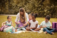 Art class at nature. Large group of children and teacher. Learning and have fun stock photography