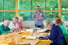 Art class with six students and teacher. Group of six female senior citizens at long table in art class with male teacher, in glasses standing near front beside royalty free stock images