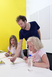 Art Class. Art teacher gives instructions to his students in a creative studio to two students in a master class product design and development royalty free stock photography