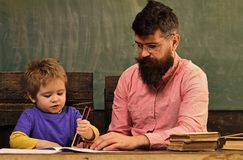 Art class for toddler, developing creativity. Busy kid drawing a picture with stack of colorful pencils. Father teaching. His son to draw royalty free stock image