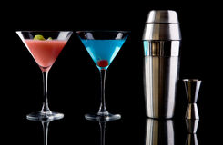 Art of cocktails. Betty Blue cocktail, Cosmopolitan cocktail, Shaker and Measure glass over black background stock images