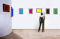 Art collector in museum. A woman standing with her back and looking at blank of one color frames in art gallery stock photography