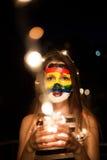 Art coloré de visage d'arc-en-ciel sur une jeune fille la nuit avec des lumières dans mains et bokeh Photo libre de droits