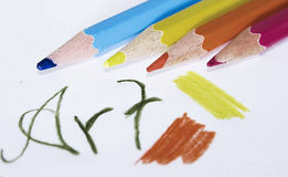 Art. Colored pencils lying on a paper with a painted text Stock Images