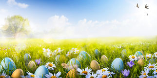 Art Colorful Easter eggs decorated with flowers in the grass. Colorful Easter eggs decorated with flowers in the grass on blue sky background