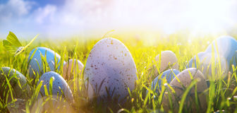 Art Colorful Easter eggs on the grass on blue sky background Stock Image