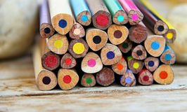 Art of colors. Colored pencils putted between two stones, on a wooden table Stock Photo