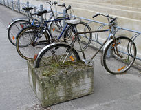 Art composition of bicycle with rear wheel stucked in concrete Stock Photo