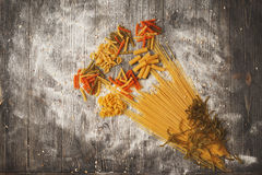 Art composition of bouquet flowers made different types pasta on a black wooden background. Art composition of bouquet of flowers made of different types of royalty free stock photography