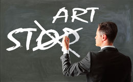 Art concept. Businessman crossing out word'stop' on chalkboard. Art concept royalty free stock photography