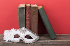 Art concept. Closeup of white classical carnival mask with vintage books and red background.  royalty free stock images