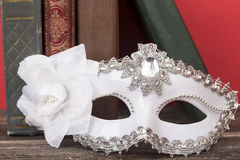 Art concept. Closeup of white classical carnival mask with vintage books and red background.  stock image