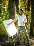 Art concept. Painting in nature. Start new picture. Painter with easel and canvas. Bearded man painter looking for. Inspiration autumn nature. Relax and hobby royalty free stock photography