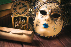 Art concept. Still life with scroll near venetian mask, old books and vintage clock on wooden table. Vintage toned image Royalty Free Stock Images