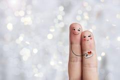 Art conceptuel de doigt d'un couple heureux L'homme donne un anneau Image courante Images stock
