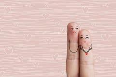 Art conceptuel de doigt Les amants est embrassant et tenant le coeur rouge barre Photo libre de droits
