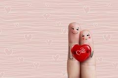 Art conceptuel de doigt Les amants sont embrassants et tenants le coeur rouge barre Images libres de droits