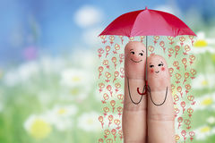 Art conceptuel de doigt Les amants sont embrassants et tenants le parapluie avec les fleurs en baisse Image courante Image stock