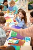 Art and craft activity in the kindergarten. Group of preschool kids hands working in day care center. stock image