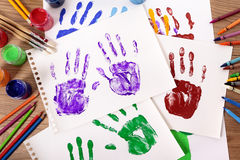 Art and craft class, child hand prints and art supplies on school desk. Painted handprints with art and craft equipment on a school table stock photo