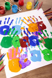 Art and craft class, hand prints and art equipment on school desk, vertical Royalty Free Stock Image