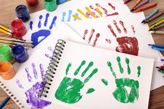 Art and craft class, hand prints painting equipment, school desk. Painted handprints with art and craft equipment on a school table stock photo