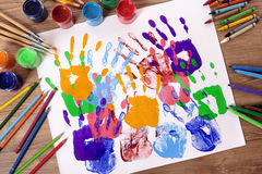 Art and craft class, hand prints, painting supplies, school desk. Painted handprints with art and craft equipment on a school table stock images