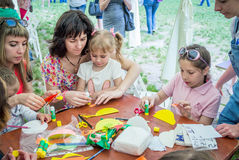 Art and craft outdoors workshop. Zaporizhia/Ukraine- May 28, 2017: Charity Family festival: girls with mothers participating at art and craft outdoors workshop Royalty Free Stock Image