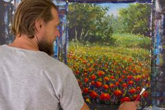 Art creative process. Artist create painting on canvas. Bearded man painter artist paints with brush a red poppies flowers in forest landscape painting on canvas stock photos