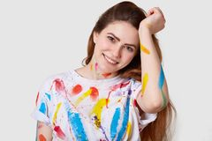 Art and creativeness concept. Positive young woman smiles gently at camera, wears white t shirt with colourful stains, busy. Creating artwork, looks happily at royalty free stock image