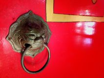 Chinese door knocker and red door in front of Chinese shrine stock photography