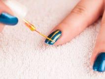 Art d'ongle - rayures d'or de peinture sur le poli bleu-foncé de base image stock