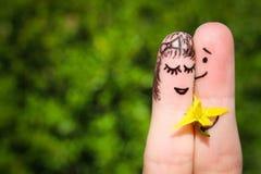 Art de doigt d'un couple heureux L'homme donne des fleurs à une femme Images stock