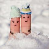 Art de doigt d'un couple heureux sur le fond de la neige Photographie stock libre de droits
