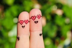 Art de doigt d'un couple heureux Un homme et une femme étreignent en verres roses dans la forme des coeurs Image stock