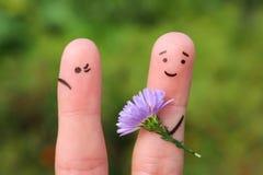 Art de doigts des couples L'homme joyeux donne le bouquet de femme des fleurs, elle n'est pas satisfaisant Images libres de droits
