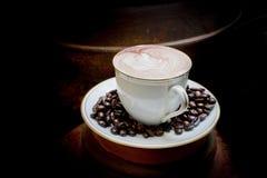 Art de Latte, café en grains de café et fond asiatique de poterie Photographie stock
