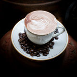 Art de Latte, café en grains de café et fond asiatique de poterie Images stock