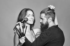 Art de maquillage homme barbu de visagiste et femme sexy image stock