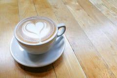 Art de mousse de cappuccino avec la forme de coeur d'amour sur la table Photographie stock libre de droits