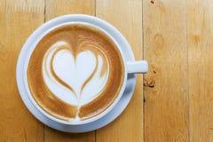 Art de mousse de cappuccino avec la forme de coeur d'amour sur la table Photos stock