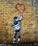 Art de pochoir de style de Banksy Enfant peignant une forme de coeur photographie stock libre de droits
