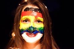 Art de visage d'arc-en-ciel sur une fille assez longue de cheveux de jeunes avec les yeux bruns Photo stock
